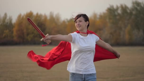 Child plays spartnats. a free girl in a red cloak with a sword in her hand plays a medieval knight in the sun. young girl plays superheroes. girl fights with a toy sword. happy childhood concept.