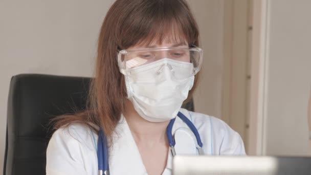 Ärztin in weißem Kittel und Schutzbrille am Laptop, Online-Beratung und Konferenz. Telemedizin, Konzept der fernmedizinischen Versorgung. Arzt kommuniziert mit Klient über virtuellen Chat