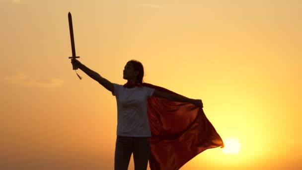 Young girl plays superheroes. Child plays Spartan In. A free girl in a red cloak with a sword in her hand plays a medieval knight in the sun. Girl fights with a toy sword. Happy childhood concept.