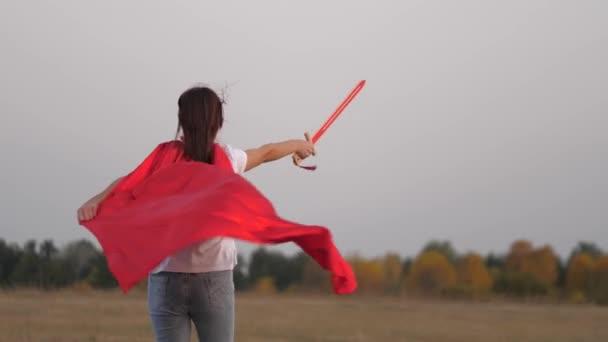 Vidám lány piros köpenyben, karddal a kezében fut át a mezőn, középkori lovagot játszva. Gyerek lovagosat játszik. Fiatal lány szuperhősöket játszik. A gyerekek játékkarddal harcolnak. Boldog gyermekkort!
