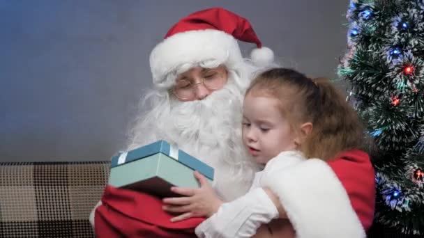 Der Weihnachtsmann sitzt mit einem kleinen Mädchen auf dem Sofa, Kind öffnet Geschenk, freut sich und umarmt Zaubergroßvater. Feiertage und Feiern Konzept. Winterurlaub für Familien mit Kindern. Frohe Weihnachten.