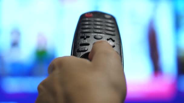 Eine Person steuert den Fernseher mit einer modernen Fernbedienung. Ein Mann sieht einen Smart-TV und bedient eine schwarze Fernbedienung. verschwommene TV-Blätterseiten
