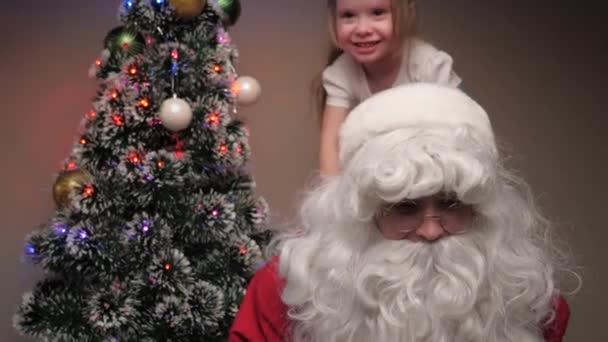Kind und Weihnachtsmann spielen zusammen, ein kleines Mädchen sitzt auf dem Rücken des Weihnachtsmannes. Der Weihnachtsmann amüsiert sich mit Kindern neben dem Weihnachtsbaum. Familienurlaub, Winterurlaub. Frohe Weihnachten.