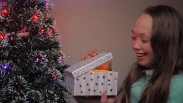 Děvče otevírá dárek od Santa Clause vedle vánočního stromečku. Dítě otevírá dárkovou krabici ve světle věnce, raduje se a usmívá. Rodinná dovolená a oslava dětí, zimní odpočinek. Veselé Vánoce.