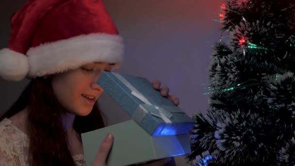 Ein Mädchen öffnet das Geschenk des Weihnachtsmannes neben dem Weihnachtsbaum. Frohe Weihnachten. Kind öffnet Geschenkbox im Lichterkranz, freut sich und lächelt. Familienurlaub und Familienfeier, Winterruhe.