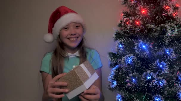 Dítě dívka v klobouku Santa Claus chytí dárek s rukama vedle vánočního stromečku. Dítě s dárkovou krabicí v rukou, raduje se a usmívá. Rodinná dovolená pro děti, zimní dovolená. Veselé Vánoce.
