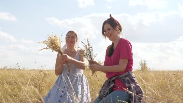 Beautiful young women in meadow collect flowers and are photographed on a smartphone in meadow. Ecotourism. Two happy girlfriends are traveling in countryside. Girls bloggers in a field with flowers.