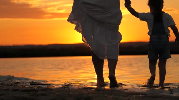 Happy family, Mom walks with child barefoot on water, joining hands in rays of a beautiful sunset. Mother with her daughter relaxing on beach. Silhouette of a woman and a child on beach at sunset.