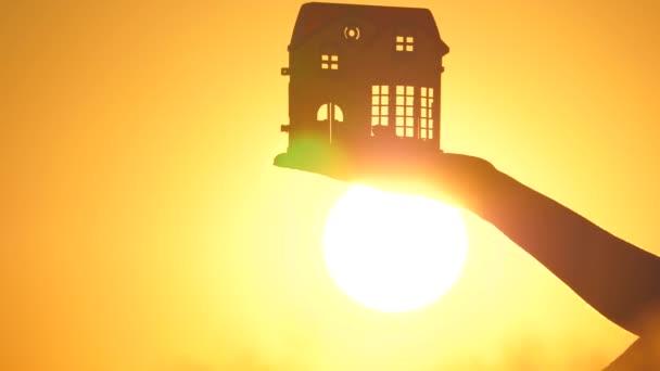 Im Handumdrehen träumt das Kind von seinem Zuhause. Schöne Familienheimkonzeption. Handsilhouette mit einem Spielzeughaus in warmen Sonnenstrahlen, Lichtstrahlen blitzen durch Fenster und Türen. Schöne Immobilien bei Sonnenaufgang.