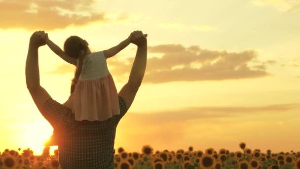 Šťastný rodinný táta a dcera si hrají na hřišti na sluníčku. Malá dcerka na ramenou farmářského otce kráčí po slunečnicovém poli v paprscích krásného západu slunce. Cesta milující rodiny