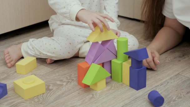 Mom and daughter play colorful cubes in childrens room. Mom and daughter are building family home. Educational games for development of children. Teaching child through play activities. Happy family