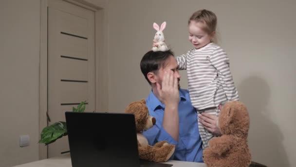Der freiberufliche Papa spielt zu Hause mit einem Kind mit Spielzeug, sie umarmen sich. Vater und Baby arbeiten von zu Hause aus. Quarantäne, Selbstisolierung. Die kleine Tochter stört den müden Papa die ganze Zeit. Glückliche Familie