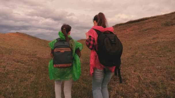 Beautiful girls tourists go together in search of adventure. Happy young women in colored raincoats travel with backpacks in the ravine. Teamwork. On a day off in nature. Healthy outdoor walks