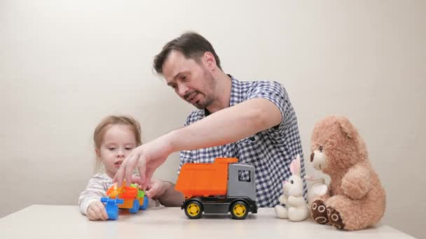 Child, girl and dad play cars toys. Happy family. Parent, dad and child are playing at home, an excavator loads dump truck with bucket. Caring father has helping his cute daughter child drive toy cars