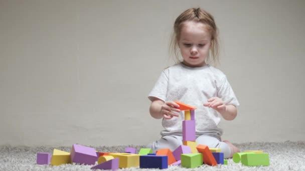 Ten kluk staví rodinný dům. Vzdělávací hry pro rozvoj dětí. Učit dítě hrát si. Šťastná rodina. Dcera si hraje s barevnými kostkami v dětském pokoji na podlaze.
