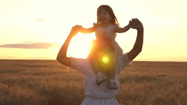 Šťastná rodina, máma a dcera si při západu slunce spolu hrají na pšeničném poli. Mladá matka s dítětem poskakuje a směje se na slunci. Koncept šťastné rodiny, dětství. Rodinná dovolená s dětmi