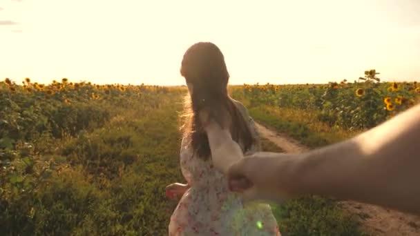 A fiatal nő vidéken utazik a barátjával, átszaladnak egy virágzó napraforgó mezején. Szabad lány és férfi kéz a kézben, séta a pályán napraforgóval naplementekor, kéz a kézben.