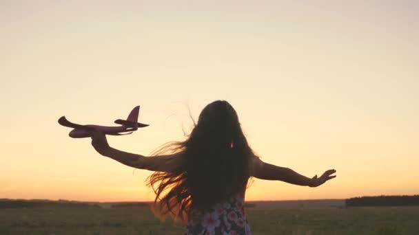 A gyerek egy játékgéppel játszik. Lassú mozgás. A lány pilóta és űrhajós akar lenni. Happy lány fut egy játék repülőgép a pályán a naplemente fény. Tinédzser álmok repülés és lesz pilóta.