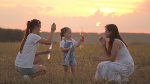 Glückliche Familienmama und Kinder spielen zusammen, pusten und fangen Seifenblasen auf dem Feld. Mutter und kleine Töchter spielen gemeinsam im Park bei Sonnenuntergang. Familie, Kindheit. Seifenblasen in der Sonne, Kindergeburtstag