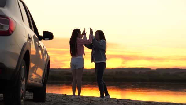 Free women travelers stand next to car on beach enjoying sunset in park, jumping and clapping rejoicing. Girls drivers stopped at campsite. Girlfriends are enjoying trip in car. Vacation, adventure