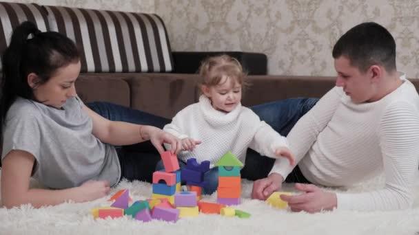 Dcera, otec a matka si hrají na stavbu rodinného domu. Šťastná rodina. Vzdělávací hry pro děti. Tati matko, dítě hraje kostky v dětském pokoji na podlaze. Učit dítě hrát aktivity