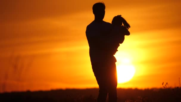 Dad is circling his beloved daughter in sun. Happy family, dad and daughter are playing in field at sunset. Father and little daughter are having fun together. Happy family and healthy childhood
