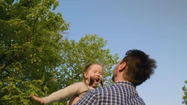 Otec vyhazuje svou šťastnou dceru v parku na modrou oblohu, dítě se směje a raduje. Táta a malé dítě si spolu hrají, smějí se a objímají. Dítě je v náručí rodičů. Víkend s tátou. Šťastná rodina.