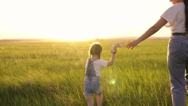 Glückliche Familie, Mutter, Kind, Tochter spielen zusammen mit einem Spielzeugflugzeug im Park auf Gras in der Sonne. Das Kind hält ein Holzflugzeug in der Hand. Teamwork von Mutter und Kind, Familienträume und Fantasien