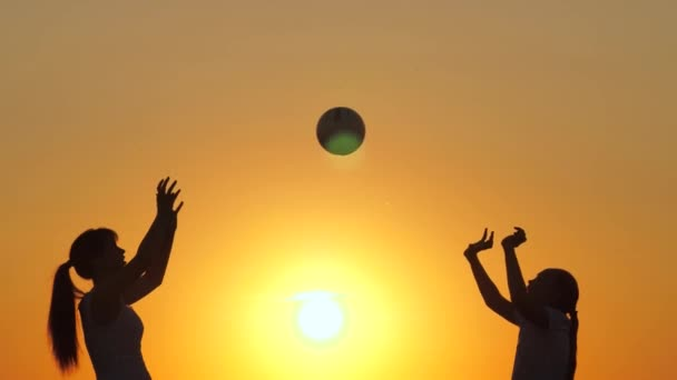 Summer family weekend. Mom and daughter are playing and throwing ball to each other under the warm sun. Happy healthy children playing with a ball at sunset. Happy family and childhood concept.
