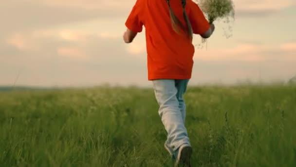 Kind läuft durch Blumenfeld. Glückliches Kindermädchen läuft auf der Straße im grünen Gras mit einem Blumenstrauß für Mama. Freudiges, kleines Mädchen träumt in der Natur. Kinderfantasien. Glückliche Familie, Sonnenuntergang