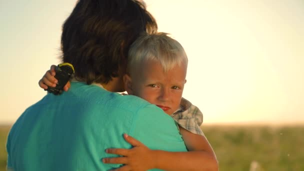 Cute affectionate little toddler boy hugs kind mother. Child loves mom. Happy son hugs his mom in summer park in sun. Adorable child hugs mommy, enjoying family happiness. Family walk with kid, nature