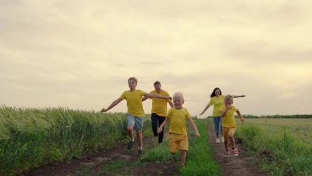 Happy family, children, sons, mom dad run, play, rejoice, enjoy nature in summer. Family teamwork. Family team, running together in field, happily waving their hands. Group of people of different ages