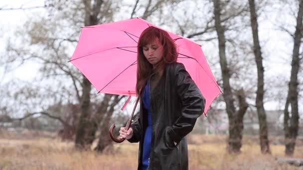 Žena s růžovým deštníkem volá po telefonu