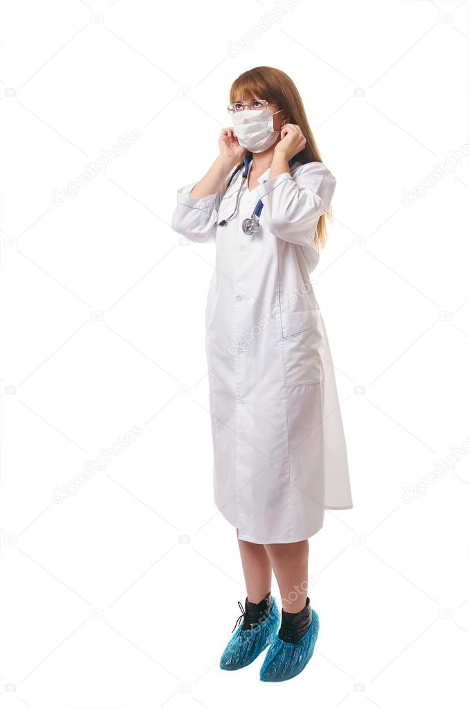The doctor in a medical mask, a white dressing gown and boot cov ...