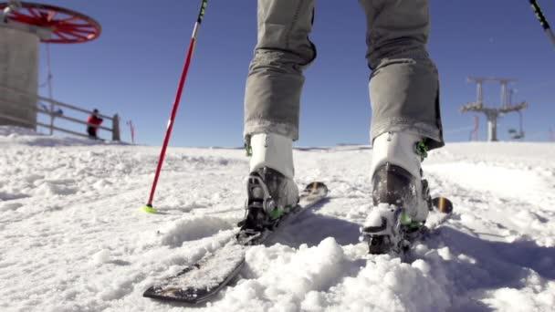 Skischuhe an Skiern befestigen