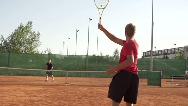 hráč udeří tenisový míček