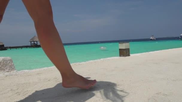 Ženské bosé nohy na pláži