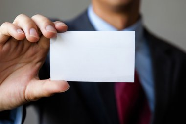 Young man in business suit holding white blank business card.