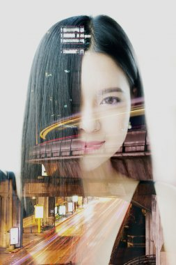 Double exposure of Asian woman dissolved with night cityscape