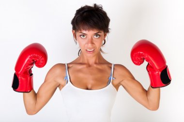 Young beautiful woman guarding while wearing boxing gloves