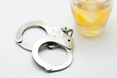Glass of whiskey and handcuffs - Drinking law concept