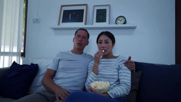 Portrét třicátých let, mladého dospělého manžela a manželky sedících doma na gauči a sledujících hororovou zábavu v televizi. Asijské strach a strach pár těšit volný čas s popcorn v útulném obývacím pokoji.