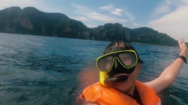Mann schwimmt in Ozean und zeigt Berge