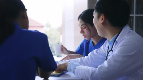 Gruppe junger asiatischer Ärzte und Krankenschwestern sitzt während der Pause in der Kantine und diskutiert einen schweren Fall von Patienten im Krankenhaus