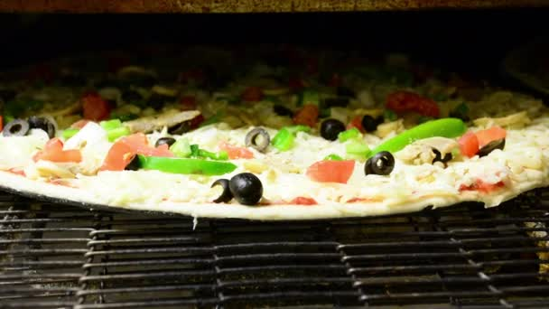A veggie pizza bakes in a restaurant