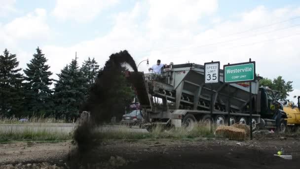 A construction worker shoots fill dirt