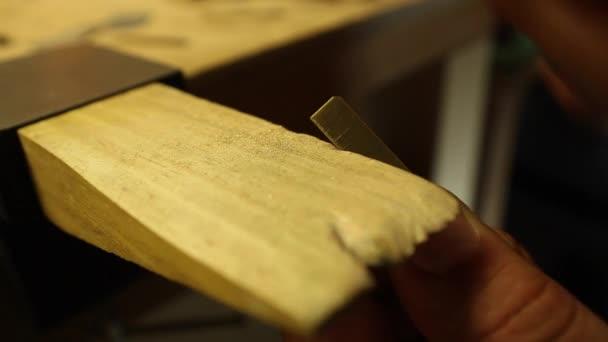 A jeweler files a piece of metal