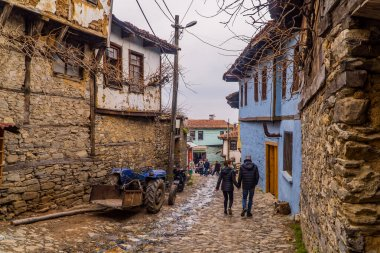 Cumalikizik (Bursa), Turkey - March 6, 2021 - a couple walking next to a tractor and medieval Ottoman houses in the village of Cumalikizik near Bursa, Turkey
