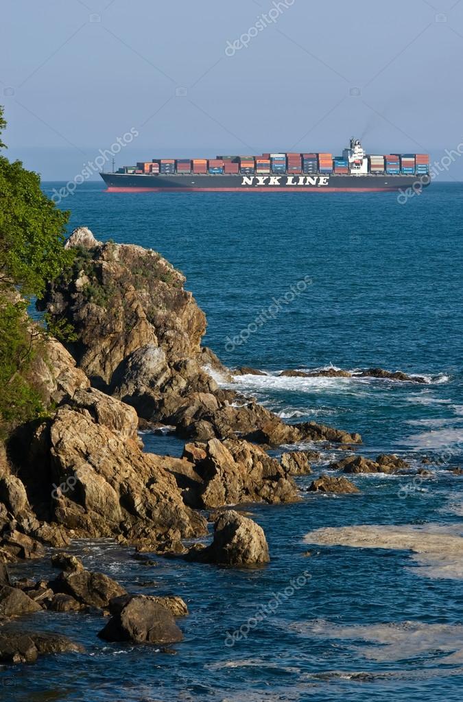 Container ship NYK Argus runs along the green coast. Nakhodka Bay. East (Japan) Sea. 27.05.2014
