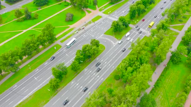City highway with a U-turn, a pedestrian crossing and a traffic light, in the middle of a green park. Aerial view
